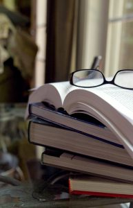 Picture of reading glasses on top of a stack of open books.